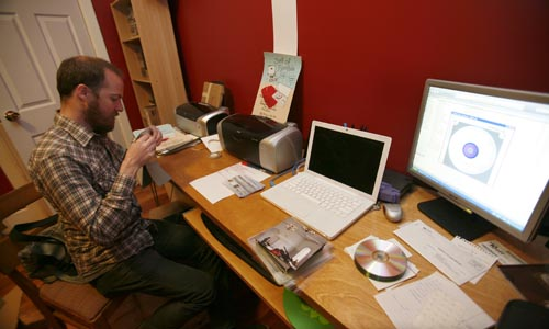 Photo of Raymond Morin, owner of Sort Of Records, making CDs